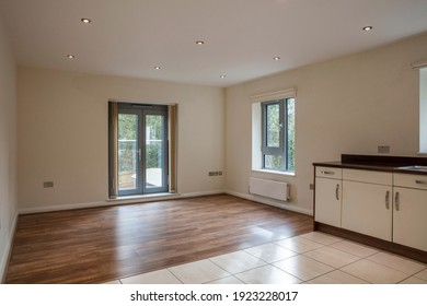 View of an empty living room area in a modern apartment with wooden flooring