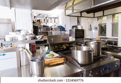 View of empty restaurant kitchen with professional equipment and products