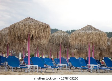 View of the empty sandy beach with blue deckchairs and parasols in the touristic place Sarti on Sithonia peninsula of Chalkidiki in Greece. Nobody on the beautiful beach.