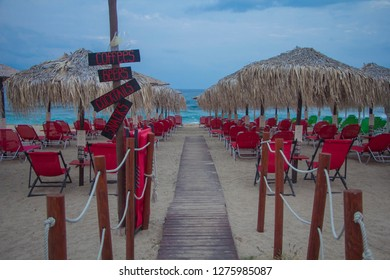 View of the empty sandy beach with red deckchairs and parasols in the touristic place Sarti on Sithonia peninsula of Chalkidiki in Greece. Nobody on the beautiful beach.