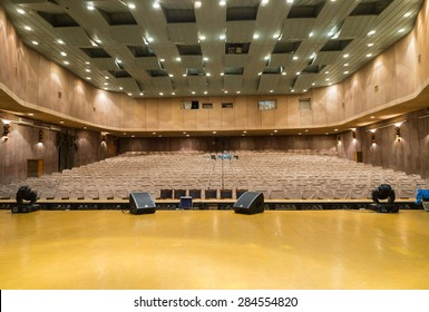 View of Empty Seats with Seat Covers Looking Toward Back of Theater from Empty Stage in Well Lit Venue