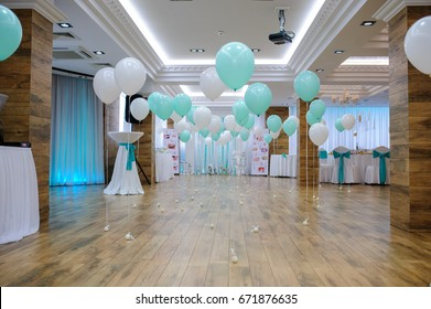 View of an empty studio restaurant decorated with white and turquoise balloons on baptism party