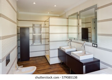 View of empty stylish bathroom with striped wall in white and black colors. Two white ceramic sink and mirrors on wall, brown floor and black door.