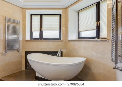 View of empty stylish bathroom in white and yellow colors. Rounded ceramic bath, brown floor and big windows with view of city.