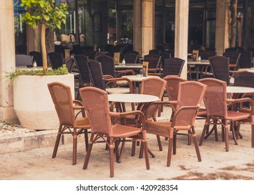 View of empty  terrace of open-air cafe with tables and chairs in old town of Budva. Montenegro. Filtered image:cross processed vintage effect.
