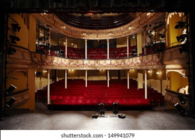 View of an empty theatre with red seats and balcony