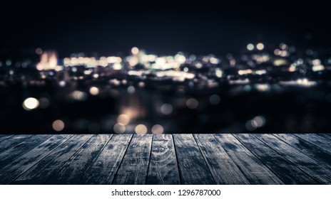 View from empty wooden plank floor above the town at night, For display or montage your product.