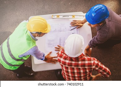 View of an Engineer and worker checking plan on construction site. Top view Construction Concept