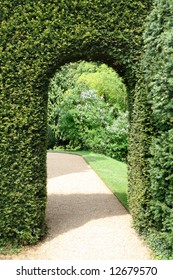 View of an English Mano Garden viwed through an archway though a Hedge