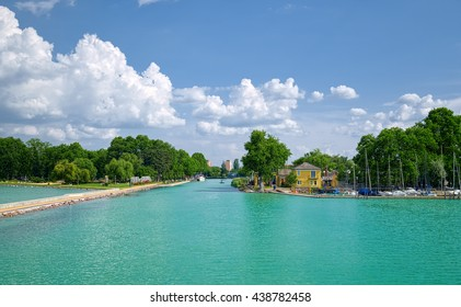 View to entrance to Siofok harbor at Balaton lake, Hungary, with crystal clear water of emerald color, green coastline, puffy clouds on sky.