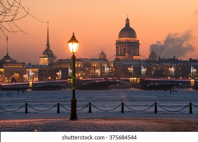 View of the evening city decorated with lights. In the foreground a street light. In the background, the main attractions - the Palace Bridge and St. Isaac sobo. Russia, Saint-Petersburg.