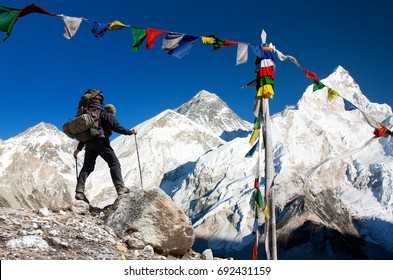View of Everest with tourist and buddhist prayer flags from Kala Patthar and blue sky - way to Everest Base Camp - Nepal