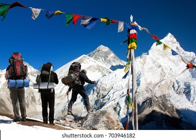 View of Everest with two tourists and buddhist prayer flags from Kala Patthar and blue sky - way to Everest Base Camp - Nepalese himalayas