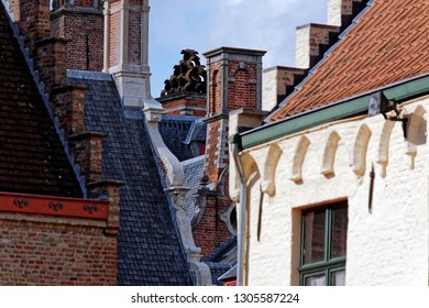 View from the exterior facade of a historic building and unique chimney in the center of the image, downtown Bruges, Belgium.