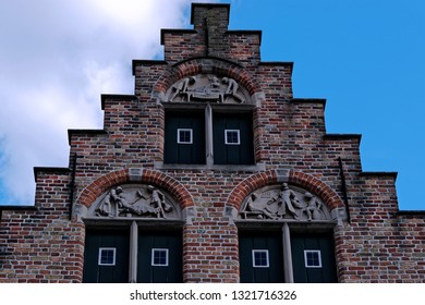 View from the exterior facade of a historic building with closed window shutters downtown Bruges, Belgium.