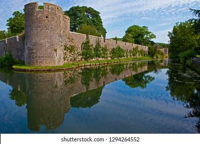 A view of the exterior wall and moat of the historic Bishops Palace in the cathedral city of Wells in Somerset, UK.