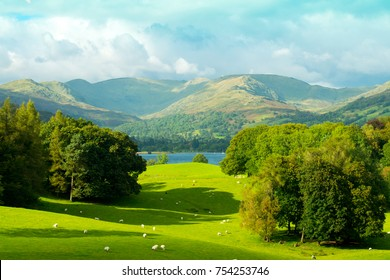 View of Fairfield Horshoe Mountain range and Lake Windermere, South Lakeland Fells, English Lake District. Blue sky view of lush green fields and scenery with mountains in the background