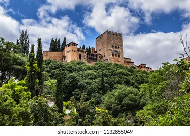 View of famous Alhambra - mediaeval Moorish palace and fortress complex from Calle Chirimias. Alhambra originally constructed as a small fortress in AD 889. Granada, Andalusia, Spain.