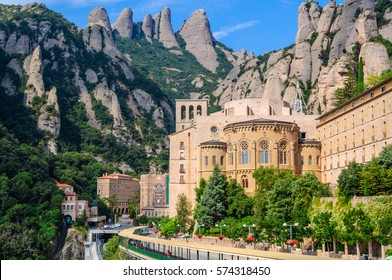 View the famous Catholic monastery of Montserrat on the background of round rocks. Blue sky. Catalonia, Spain.