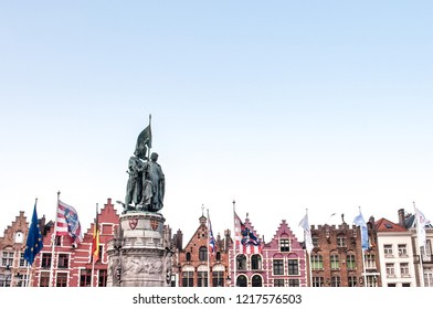 A view of the famous colorful Medieval Flemish buildings in The Markt (the market square)in Bruges with flags and statue. West Flanders, Belgium, Europe
