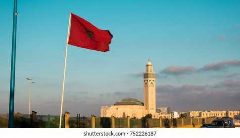 View of the famous Hassan II mosque and a waving moroccan flag against sky - Casablanca - Morocco