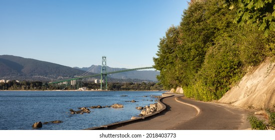 View of the Famous Lions Gate Bridge from Seawall at Stanley Park in a modern city. Downtown Vancouver, British Columbia, Canada. Sunny Summer Sunset.