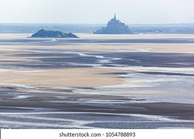 View of famous Mont Saint-Michel bay with abbey and neighboring island at the low tide with quicksands on the foreground, Normandy, France