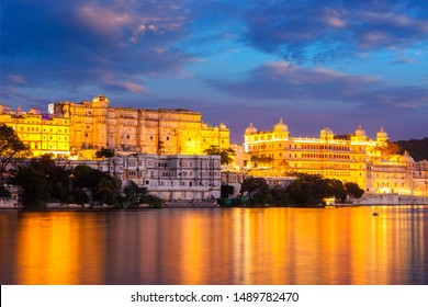 View of famous romantic luxury Rajasthan indian tourist landmark - Udaipur City Palace in the evening twilight with dramatic sky - panoramic view. Udaipur, India