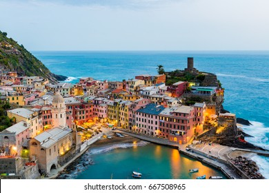 view of famous travel landmark destination Vernazza, small mediterranean old sea town with harbour coast and castle,Cinque terre National Park, Liguria, Italy. Summer early morning with street lights