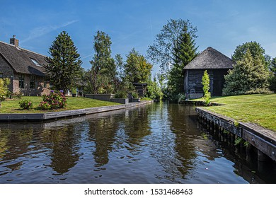 """View of famous typical Dutch village in Giethoorn, Netherlands. Beautiful houses, plants and flowers in village known as """"Venice of the North""""."""