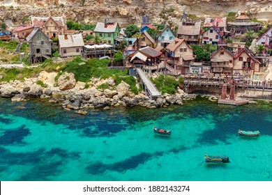 View of the famous village of Popeye with colorful wooden houses and the Gulf of Malta.