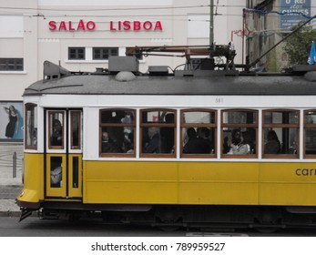 View of the famous yellow tramway at lisboa Portugal. The old tram with cables is circulating on the street with many people on board. The sunny picture has been taken on 4th march 2010.