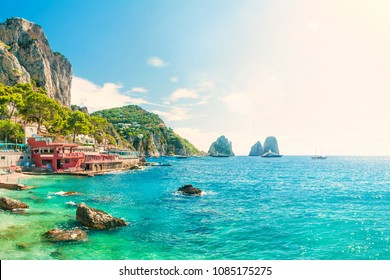 view of faraglioni rocks at sunset from Marina Piccola beach on summer day with turquoise blue waters and beachfront cafes, Capri, Italy
