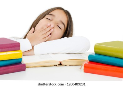 View of fatigue pretty schoolgirl covers mouth with palm, yawns as wants to sleep, being tired of studying, sits at white table, reads books. Isolated on white background