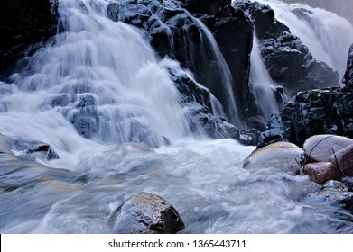 View featuring gushing water at a high flow rate cascading over the bedrock edges and boulders downstream disappearing into a crevice along the wet surface of granite rocks with huge water splash