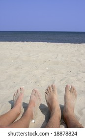 View of feet on a beach against the sea