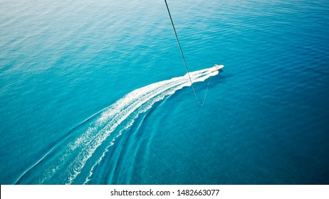 View of feet parasailing with the speed boat in the sea background.