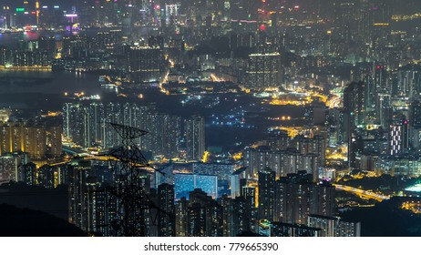 View from Fei ngo shan Kowloon Peak night timelapse Hong Kong cityscape skyline. Tall buildings and power transmission lines. 4K