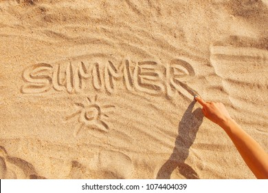 View of female hand drawing word summer on the sand, top view.