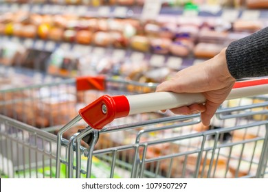 View of a female hand with pushcart in supermarket. The racks with the consumer goods in blur. Shallow depth of field