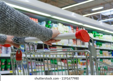 View of a female hands on pushcart in supermarket. The racks with the consumer products in blur