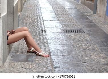View of a female legs and arms with white sandals and holding her phone