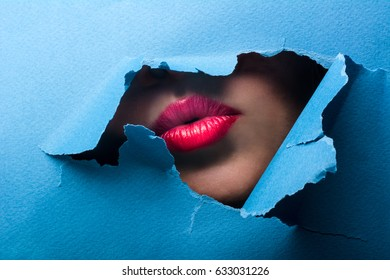 A view of the female lips through a hole in a paper blue background.