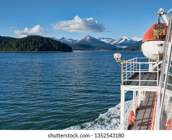 View from a ferry in Southeast Alaska in summer on a sunny day.