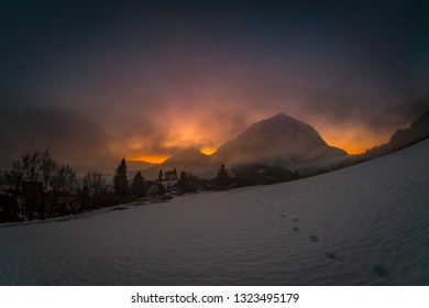 View from a field near village Puergg to dramatic sunset over mountain Grimming in Styria, Austria