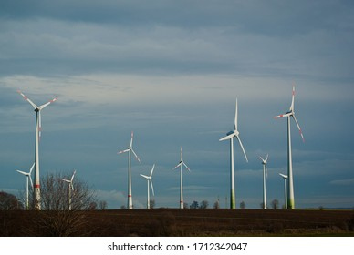 View of the field in winter. Huge white windmills stand against the grey sky in clouds.