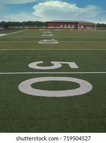 The view from the fifty yard line on an astroturf football field.