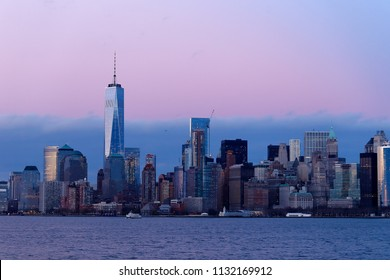 A view of the financial district of New York City across the Hudson River late in the afternoon.