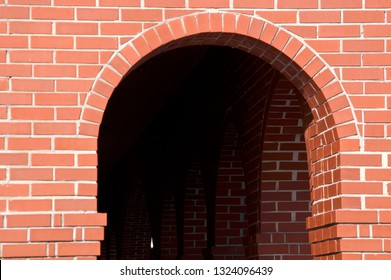 View of a finely crafted brick archway leading into a tunnel of more arches.