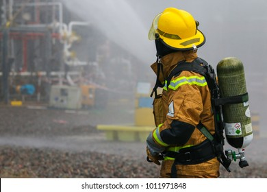 View of a fire fighter with compressed air tank. Visible water mist in the background.